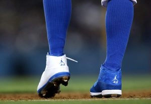 Carl Crawford of the Los Angeles Dodgers wears one blue shoe and one white shoe, both with Jacke Robinson's number 42 on the back, as he stands on first base in the game agaisnt the San Diego Padres at Dodger Stadium on April 15, 2013 in Los Angeles, California. All uniformed team members are wearing jersey number 42 in honor of Jackie Robinson Day. (Stephen Dunn/Getty Images/AFP)