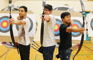 BRIAN BAKER/TOWN CRIER GOOD AIM: John Polanyi Collegiate's archery team, from left, Aditya Harchand, Shaz Asher and Johnpark Reyes, prep their bows. The school earned its first athletic banner in Boys' Standard Class at the Ontario High School Archery Invitational Tournament, May 14–15.