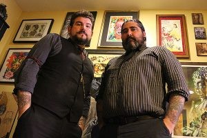 BRIAN BAKER/TOWN CRIER MEN OF ART: George Brown III, left, and Reverend Matt Ellis stand inside their lair at Seven Crowns Tattoos on Yonge St. just north of Eglinton Ave. The duo started the shop five years ago, with the hopes of turning the hood into a Queen Street North, (Brown admits), but have still supplied residents of midtown with plenty of ink and imaginative works.