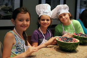 BRIAN BAKER/TOWN CRIER SWEET SMILES: Karin Bider, Liel Amato and Morgan DiNardo help prepare the dessert for judges during the Moms Helping Moms campaign cook-off at The Chef Upstairs.