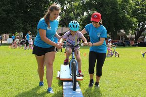 BRIAN BAKER/TOWN CRIER A HELPING HAND: Instructors Hailey Burton, left, and Colleen Morawetz help Gennavive Marshall, 7, ride her bike over an obstacle during the Pedalheads camp in Trace Manes Park, July 3.