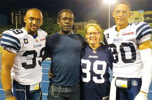 PHOTO COURTESY MARLANE AND DONOVAN BLACK FOOTBALL AND FAMILY: Toronto Argonauts safety Matt Black, left, and his brother Eric, are joined by parents Donovan and Marlane before a recent CFL game. Mom and dad are giddy that both of their sons are playing professional football on the same team.