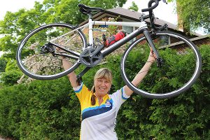 BRIAN BAKER/TOWN CRIER  GETTING A LIFT: Jana Pokorna of Leaside, raises her new KindHuman Kampionne bike above her shoulders. The $2,500 set of wheels was a gift from Gavin Brauer and the crew at KindHuman after her bike, used for the Ride to Conquer Cancer was stolen June 4.
