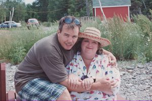 PHOTO COURTESY RAYMOND RATCHFORD A TRIP DOWN EAST: In this undated photo, Raymond Ratchford, left, hugs his friend Rita MacNeil while visiting their home province of Nova Scotia.
