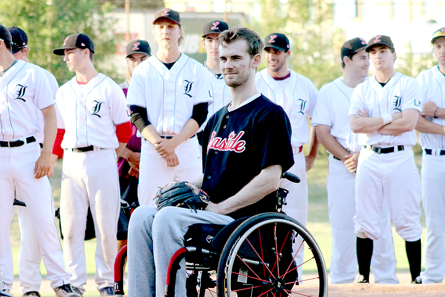BRIAN BAKER/TOWN CRIER INSPIRATIONAL: Lee Melymick, who was paralyzed from the waist down in a workplace accident, is joined by his former teammates as he prepares to throw the opening pitch.
